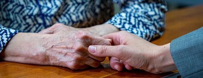Una persona mayor da la mano a una persona más joven
